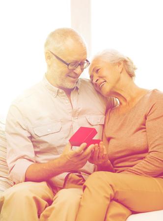 vecchiaia: felice coppia senior con confezione regalo rosso a casa