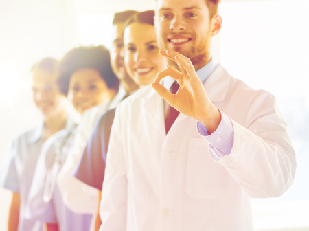 health care and medicine: gesture, education, people, health care and medicine concept - group of happy doctors showing ok hand sign at hospital Stock Photo