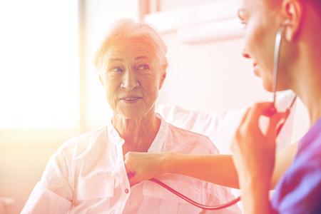 concetto di medicina, l'età, il supporto, l'assistenza sanitaria e la gente - medico o l'infermiere con stetoscopio visita donna di alto livello e che controlla il suo respiro o battito cardiaco al reparto ospedaliero
