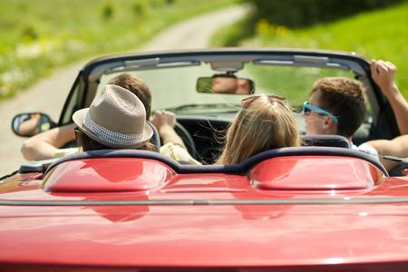 Autoreise, Reise, Ferien und Leutekonzept - glückliche Freunde, die in konvertierbares Auto am Sommer fahren