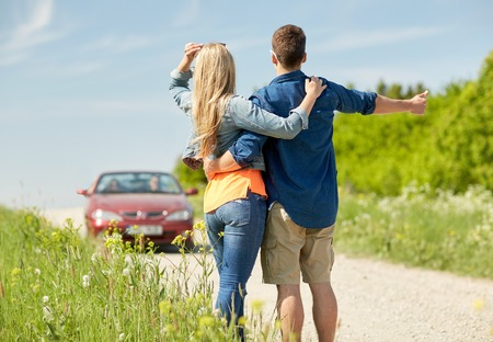 hitched: road trip, hitchhike, travel, gesture and people concept - happy couple hitchhiking and stopping car at countryside Stock Photo