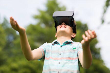 niños jugando videojuegos: la infancia, la realidad aumentada, la tecnología y el concepto de la gente - muchacho con auriculares virtual o gafas 3d que juega el juego al aire libre en verano