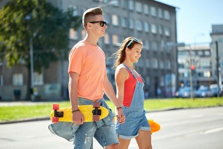 pareja de adolescentes: pareja de adolescentes con monopatines en calle de la ciudad