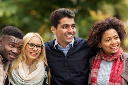 personas abrazadas: group of happy international friends outdoors Foto de archivo