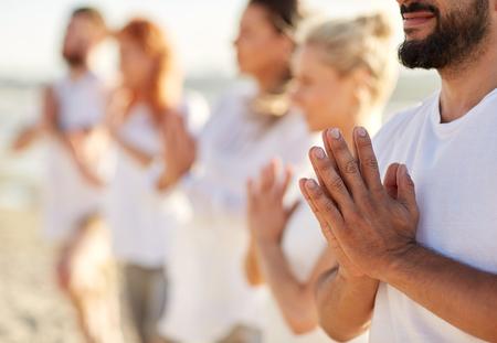 groep van mensen die yoga of mediteren op het strand Stockfoto