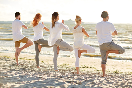 group of people making yoga in tree pose on beach