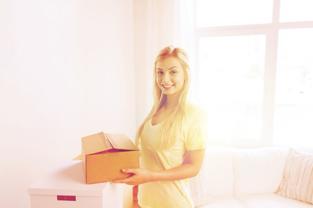 nice accommodations: smiling young woman with cardboard box at home Stock Photo