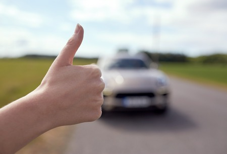 hitchhiker stopping car with thumbs up hand sign