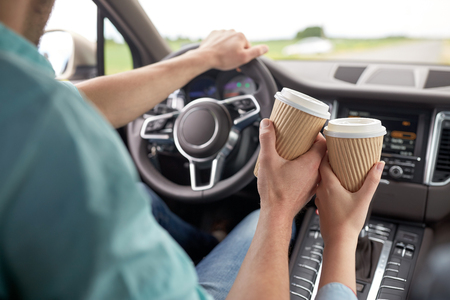 driving a car: close up of couple driving in car with coffee cups