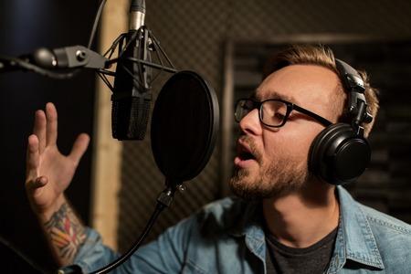 Man met een koptelefoon zingen op opnamestudio Stockfoto - 68985520