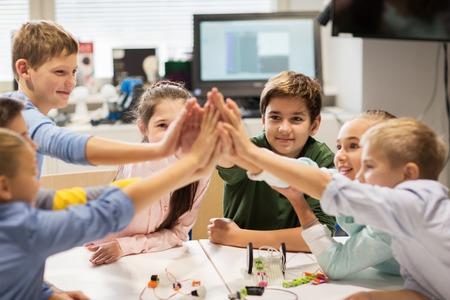 Glückliche Kinder hoch fünf in der Robotik Schule machen Standard-Bild - 68985548