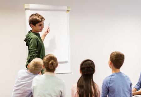 Student jongen met marker schrijven op flip boord Stockfoto - 68985553