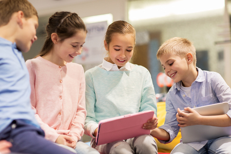 elementary school: group of happy children with tablet pc at school Stock Photo