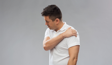 middle joint: unhappy man suffering from pain in shoulder Stock Photo