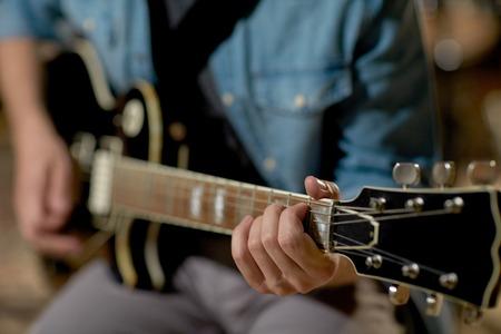 rehearsal: close up of man playing guitar at studio rehearsal