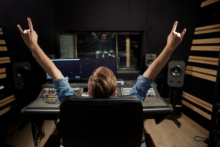 man at mixing console in music recording studio Imagens