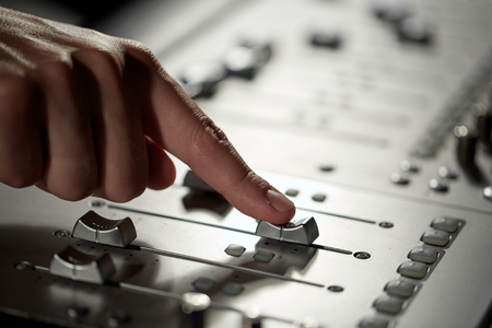 adjuster: hand with mixing console in music recording studio