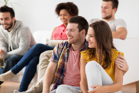 people watching: happy couple with friends watching tv at home