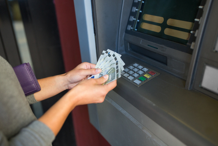hand with money: close up of hand withdrawing money at atm machine