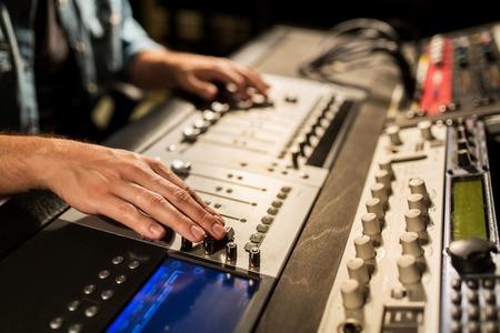 postproduction: man using mixing console in music recording studio
