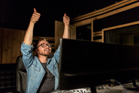 postproduction: man at mixing console in music recording studio Stock Photo