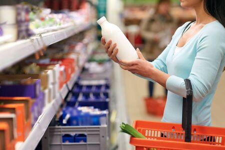 Frau mit Milchflasche in Lebensmittelgeschäft oder Supermarkt