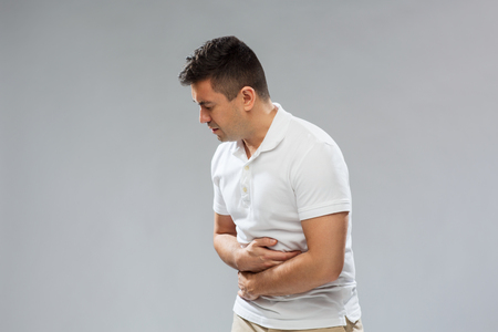 suffering: unhappy man suffering from stomach ache
