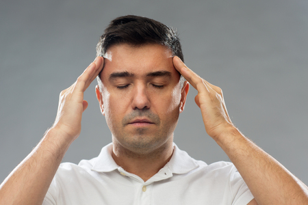 concentrating: man suffering from head ache or thinking Stock Photo