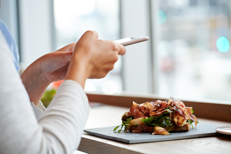 hand phone: woman with smartphone and ham salad at restaurant