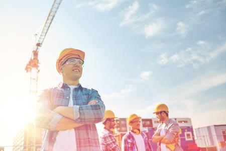 ビジネス、建築、チームワークと人コンセプト - 笑顔 hardhats 建設現場で建設業者のグループ