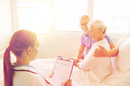 Hospital care: medicine, age, health care and people concept - senior woman, man and doctor with clipboard at hospital ward Stock Photo