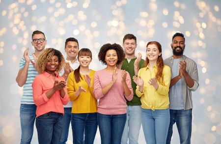 diversity, race, ethnicity and people concept - international group of happy smiling men and women applauding over holidays lights background Stock Photo