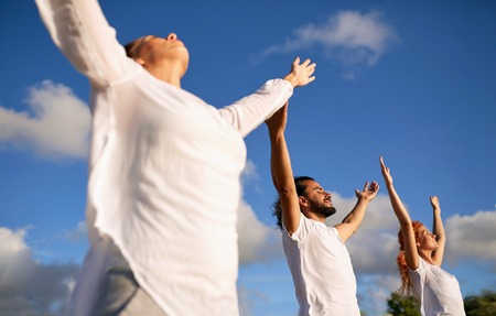 group of people making yoga or meditating outdoors