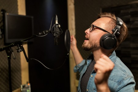 audition: man with headphones singing at recording studio