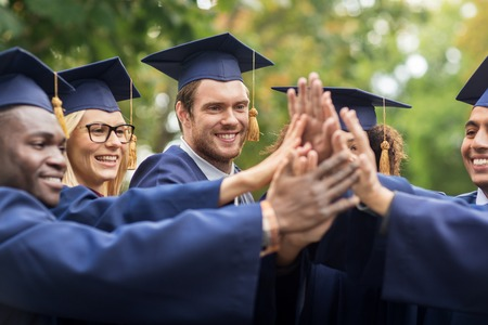 happy students in mortar boards making high five Stock Photo