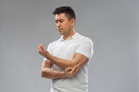 middle joint: unhappy man suffering from pain in hand