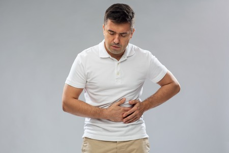 unhappy man suffering from stomach ache