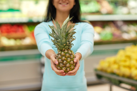 purchaser: woman with pineapple at grocery store