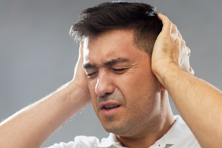 close up of man suffering from noise closing ears