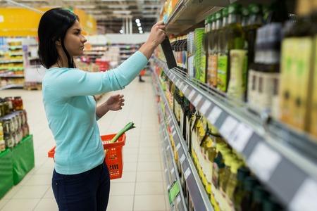 Frau wählt Olivenöl im Supermarkt oder Lebensmittelgeschäft