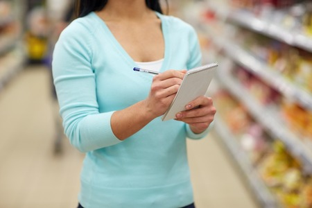 purchaser: woman with notebook shopping at supermarket Stock Photo