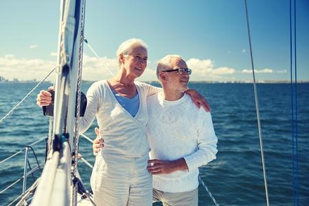 viaje familia: senior couple hugging on sail boat or yacht in sea