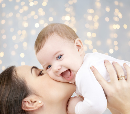 happy mother kissing adorable baby photo