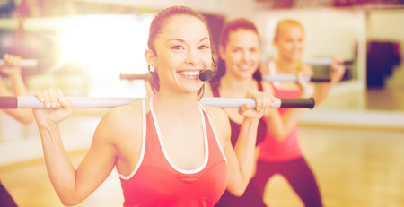 group of smiling people working out with barbells Stock Photo