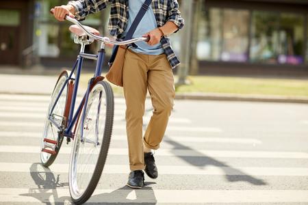 fixed: hombre joven con bicicleta fija del engranaje en el paso de peatones Foto de archivo