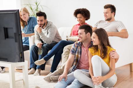 amigos felices con palomitas viendo la televisión en casa Foto de archivo