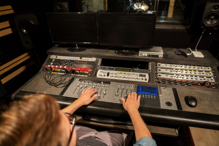 adjuster: man at mixing console in music recording studio Stock Photo