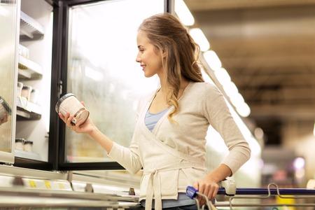 食料品店の冷凍庫でアイスクリームを持つ女性 写真素材