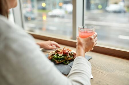aperitive: woman with salad and glass of drink at restaurant Stock Photo