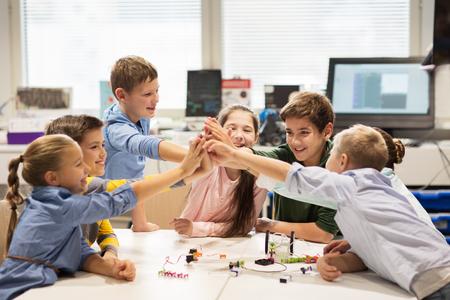 로봇 공학 학교에서 하이 파이브를 만드는 행복한 아이들